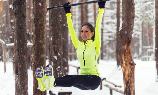 Fit girl training abs by raising legs on a horisontal bar. Fitness woman workout doing exercises outdoor winter park