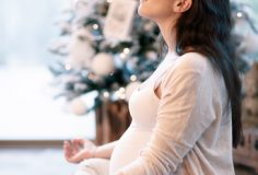 Pregnant woman meditating at home near beautiful decorated Christmas tree, sitting in lotus pose with closed eyes, body care and inner peace