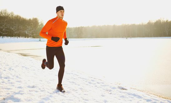 Young man running at winter in park