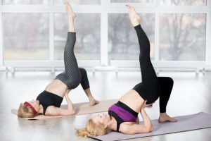 "Fitness, stretching practice, group of two attractive fit mature women working out in sports club, ""warming up"", doing backbend pose, one-legged shoulder bridge exercise in class, full length"