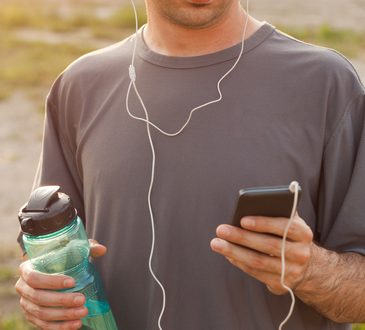 photodune-14711772-man-setting-the-music-playlist-for-the-workout-xs1