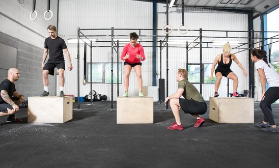 A group trains box jump with personal trainers at a crossfit center.