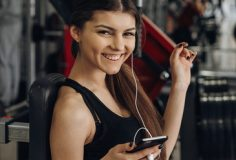 Beautiful girl with a phone in the gym
