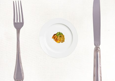 Diet concept: Stop Eating! Big fork and knife and small portion of the meal