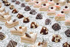many cream sponge cakes and tapered sweets on buffet table, shallow DOF