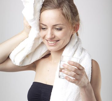Woman Drinking Water wearing sportswear and towel