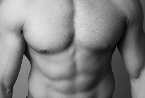 Abs of a muscular man on grey background