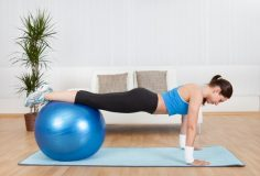 Attractive Woman Exercising With Exercise Ball At Home.