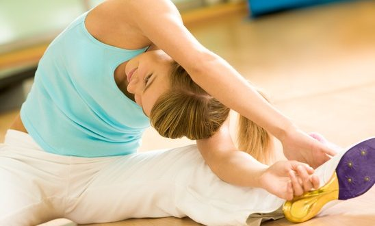 Image of sporty girl sitting on the floor and doing stretching exercise