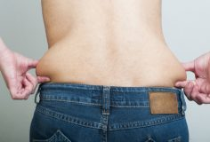 Woman pinching fat from her waist. Back shot