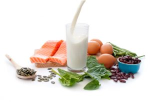 Protein rich foods including eggs, spinach leaves and pumpkin seeds with a glass of pouring milk in the middle