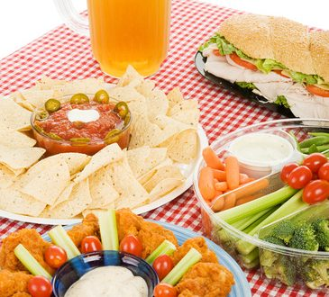 Table set with party snack food platters and a pitcher of beer.