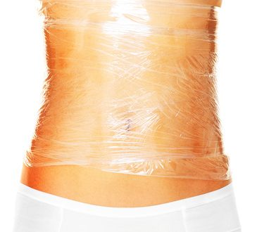 A picture of a sexy female body wrapped around with foil to reduce cellulite over white background