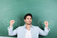 Thoughtful male teacher with clenched fists against dumbbells drawn on chalkboard