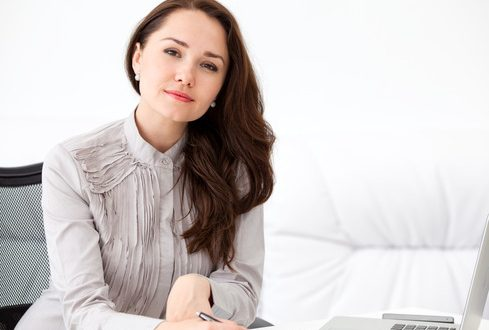 Portrait of beautiful young business woman sitting at desk at office