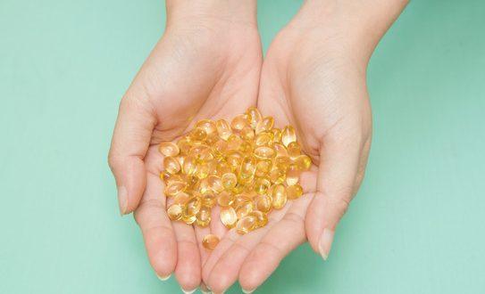 Vitamin Omega-3 fish oil capsules on a hand