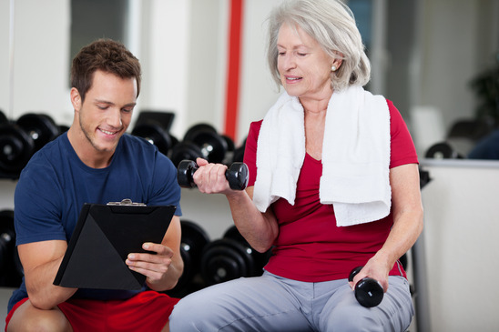 Trainer instructing a senior woman in the gym