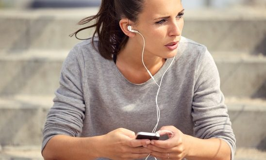 Young female athlete resting and listening to mp3 music outdoors