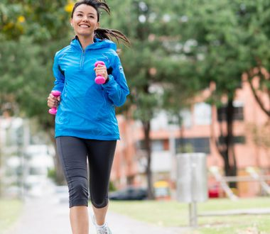 Happy woman running outdoors with extra weight