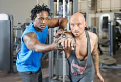 Personal fitness trainer giving instructions to a man, working out in a gym, focus on the hands