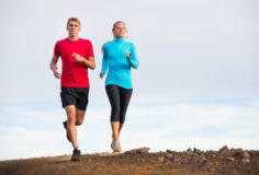 Fitness sport couple jogging outside, training together outdoors. Running on nature trail
