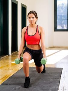 Photo of a beautiful female doing lunges with dumbbells.