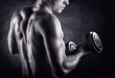 Bodybuilder training with dumbbells on black background. Rear view