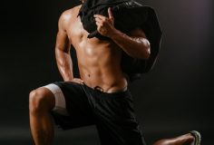 Photo of a muscular man doing lunges with a sand bag.