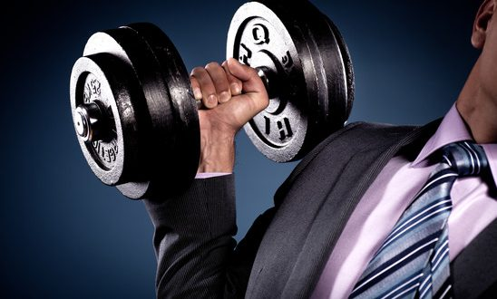 Suited man holding a heavy barbell