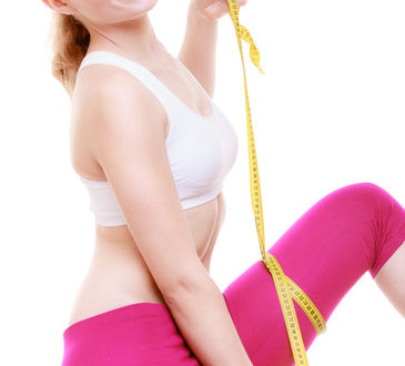 Body care diet weight loss concept. Fitness girl sporty smiling woman measuring her thigh with measurement tape isolated on white background