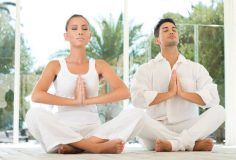 Young Couple Sitting In A Lotus Pose And Meditating While Exercising At Yoga