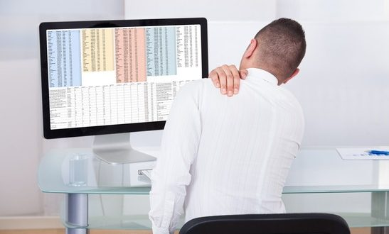 Rear view of young businessman with shoulder pain using computer at office desk