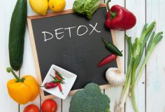 Detox handwritten on a chalkboard surrounded by fresh vegetables
