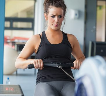 Exhausted woman training on row machine in gym