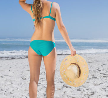 Rear view of fit woman in bikini on beach holding sunhat on a sunny day