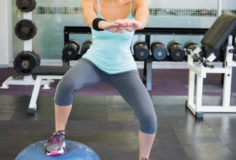 Fit brunette using bosu ball for squats at the gym
