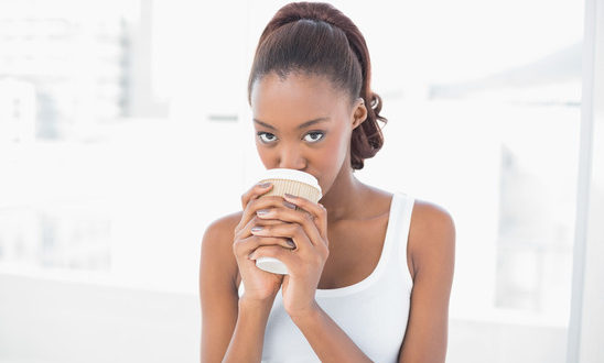 Cute sporty model drinking coffee in bright fitness studio