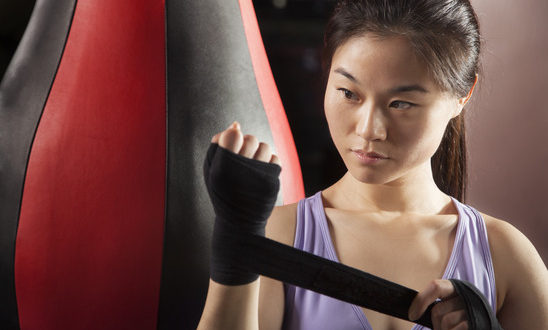 Young confident female boxer wrapper her wrists in the gym