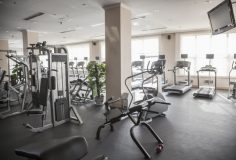 Large, bright gym with workout equipment.
