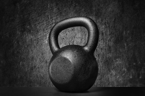 Black and whit image of a rough and tough heavy 30 kg 66 lbs cast iron kettlebell.
