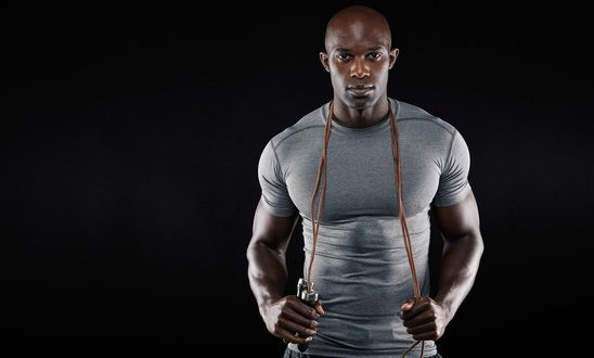 Handsome muscular man posing with jumping rope on black background. African fitness model with skipping rope.