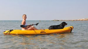 young woman and her rottweiler on a sea kayak
