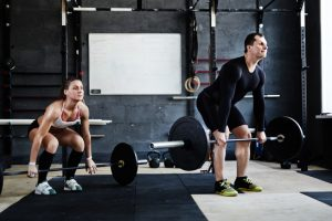 Young man and woman lifting weight