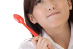 Eating concept with cute business woman holding tablespoon and smile on white background.