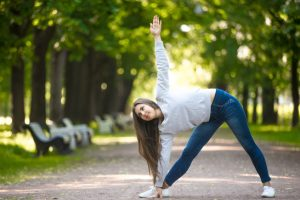Smiling beautiful sporty young woman working out in park alley, doing stretching exercise, standing in Triangle yoga pose, Trikonasana, full length