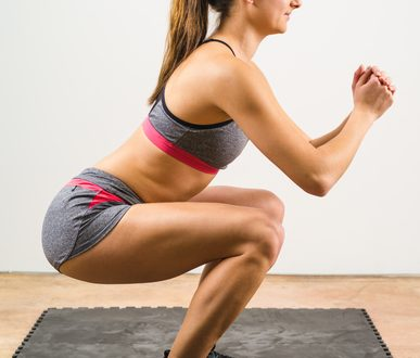 Photo of a young woman exercising and doing a isometric squat on a black floor mat.