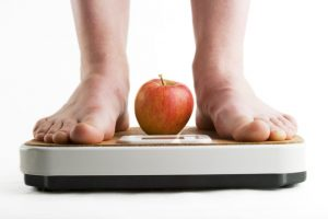 A pair of female legs standing on a bathroom scale with an apple between them.