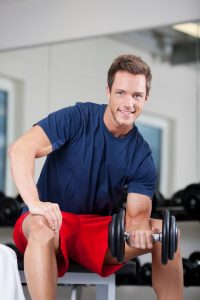 Happy muscular young man lifting weights in the gym
