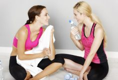 Two young friends resting after long workout at gym