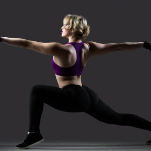 Beautiful dancer girl in sportswear doing lunge exercises with stretched arms, balance practice, on black background low key studio shot, side view